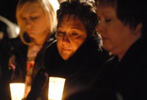 Kathleen Savio's sisters Sue Doman, left, and Anna Doman, right, participate in a candlelight vigil to commemorate the one-year anniversary of Stacy Peterson's disappearance and to remember their sister who died in March 2004. Nearly 100 people gathered Oct. 28 in Bolingbrook for a silent march from Savio's home to Peterson's home. Photo by Erica Benson